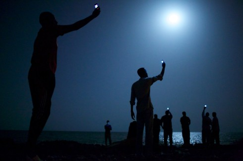 African migrants on the shore of Djibouti City at night raise their phones in an attempt to catch an inexpensive signal from neighboring Somalia—a tenuous link to relatives abroad. Djibouti is a common stop-off point for migrants in transit from such countries as Somalia, Ethiopia and Eritrea, seeking a better life in Europe and the Middle East. (Photo by John Stanmeyer) - Source: World Press Photo